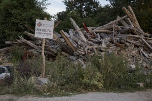 """A panel with the slogan """"no selfie"""" is seen among the rubble of a collapsed building almost one year after the earthquake in the village of Cascello, central Italy on July 31, 2017. Italy was struck by a powerful 6.2 magnitude earthquake in the night of August 24, 2016 which has killed at least 297 people and devastated dozens of houses in the Lazio village of Amatrice and other Amatrice fractions."""