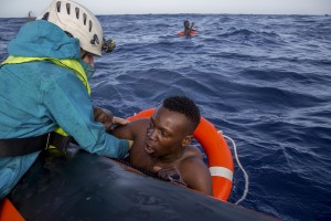 A member of German NGO Sea-Watch (L) helps a migrant to board a boat after he was recovered in the Mediterranean Sea on November 6, 2017. During a shipwreck, five people died, including a newborn child. According to the German NGO Sea-Watch, which has saved 58 migrants, the violent behavior of the Libyan coast guard caused the death of five persons. Alessio Paduano