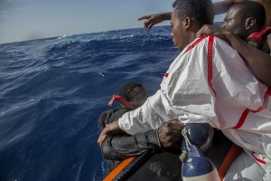 A migrant tries to board a boat of the German NGO Sea-Watch in the Mediterranean Sea on November 6, 2017. During a shipwreck, five people died, including a newborn child. According to the German NGO Sea-Watch, which has saved 58 migrants, the violent behavior of the Libyan coast guard caused the death of five persons.