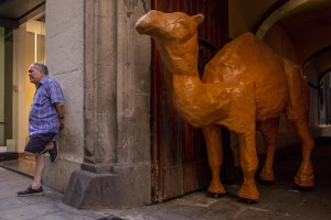 A man is portrayed near the statue of a camel in the Raval district in Barcelona, Spain on July 12, 2018. The Raval is one of the most multicultural and colorful neighborhoods in the city and it hosts numerous artists and galleries.