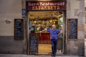 A man outside his bar in the Raval district in Barcelona, Spain on July 12, 2018. The Raval is one of the most multicultural and colorful neighborhoods in the city and it hosts numerous artists and galleries.