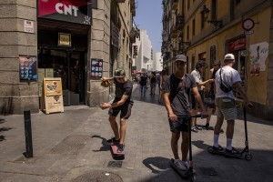 People walk in the streets of Raval district in Barcelona, Spain on July 12, 2018. The Raval is one of the most multicultural and colorful neighborhoods in the city and it hosts numerous artists and galleries.
