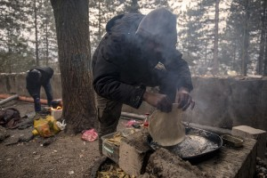 Migrant prepare food outside an abandoned building in the outskirts of the Bosnian city of Bihać, Bosnia and Herzegovina on November 28, 2018.