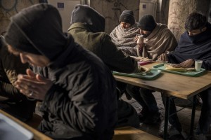 Afghans and Pakistanis migrants have a breakfast inside an abandoned building near a park in Bihać, Bosnia and Herzegovina on November 28, 2018.