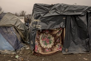 A migrant smokes a cigarette inside a refugee camp in Velika Kladusa, Bosnia and Herzegovin on November 30, 2018.