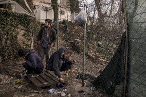 Migrants wash their shoes outside an abandoned building where they took refuge in the outskirts of the Bosnian city of Bihać, Bosnia and Herzegovina on November 29, 2018.