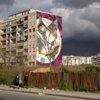 """People walk near the mural entitled """"'O sciore cchiù felice"""" (the happiest flower) realized by the Italian street artist """"Fabio Petani"""" inside the so called """"Park of murals"""" in Ponticelli, near Naples, Italy on April 8, 2019. An artistic redevelopment and social regeneration program promoted by INWARD (observatory on urban creativity) has been starting since 2015."""