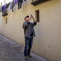 "A tourist takes a picture during the street art tour organized by the cultural association ""400 ml"" in Naples, Italy on March 24, 2019. Napoli Paint Stories street art and graffiti tour is a touristic walk in the neapolitan historical center through murales,stencils,slogans,posters and graffiti to discover urban art."