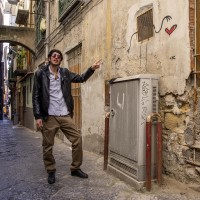 "A tour guide shows a graffiti of the florentine street artist ""Exit Enter k"" in the alleys of the Neapolitan historical center, during a street art tour organized by the cultural association ""400 ml"" in Naples, Italy on March 24, 2019. Napoli Paint Stories street art and graffiti tour is a touristic walk in the neapolitan historical center through murales, stencils, slogans, posters and graffiti to discover urban art."
