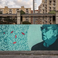 "A mural depicting Danilo Dolci, who was an Italian sociologist, poet, educator and activist of non-violence, in Scampia district, Naples, Italy on March 9, 2019. The mural is located near the ""garden of non-violence and the five continents"" and is part of a project realized by ""Raro"" and Fabio della Ratta ""biodpi"",  with the collaboration of three boys from Gambia."