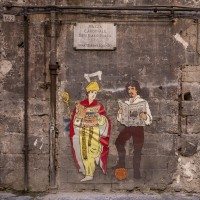"A stencil depicting Saint Januarius and the painter Caravaggio realized by the Neapolitan artist ""Roxy in the box"" is seen on a wall of the historical center of Naples, in Italy on March 19, 2019."