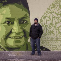 "A portrait of the street artist Gianluca ""Raro"" near a mural depicting Rigoberta Menciù, a Guatemalan pacifist who received the Nobel Peace Prize in 1992, in Scampia district, Naples, Italy on March 9, 2019. The mural is located near the ""garden of non-violence and the five continents"" and is part of a project realized by ""Raro"" and Fabio della Ratta ""biodpi"",  with the collaboration of three boys from Gambia."