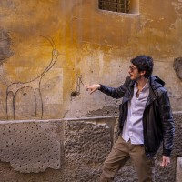 "A tour guide shows a graffiti of the street artist ""Exit Enter k"" in the alleys of the Neapolitan historical center, during a street art tour organized by the cultural association ""400 ml"" in Naples, Italy on March 24, 2019. Napoli Paint Stories streetart and graffiti tour is a touristic walk in the neapolitan historical center through murales, stencils, slogans, posters and graffiti to discover urban art."