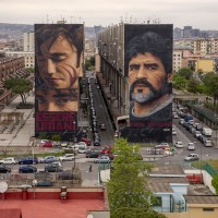 "Two murals depicting the Argentine football player Diego Armando Maradona and a child realized by the Italian street artist ""Jorit"" are seen on the facades of two buildings in San Giovanni a Teduccio, near Naples, in Italy on May 9, 2019."