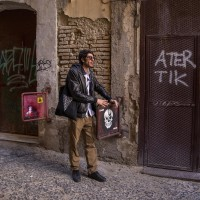 "A tour guide shows a graffiti of the French street artist ""C215"" in the alleys of the Neapolitan historical center, during a street art tour organized by the cultural association ""400 ml"" in Naples, Italy on March 24, 2019. Napoli Paint Stories streetart and graffiti tour is a touristic walk in the neapolitan historical center through murales, stencils, slogans, posters and graffiti to discover urban art."