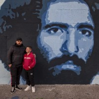 "Gaetano (sx) and Giulio (dx) are portrayed near a mural depicting Claudio Miccoli, who was an Italian environmentalist died in 1978 afters the attack by neo-fascist thugs, in Scampia district, Naples, Italy on March 9, 2019. The mural is located near the ""garden of non-violence and the five continents"" and is part of a project realized by ""Raro"" and Fabio della Ratta ""biodpi"",  with the collaboration of three boys from Gambia."