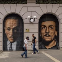 "People walk near two murals of the actor, playwrighter and director Eduardo De Filippo realized by the Italian street artist ""Jorit"" to celebrate the thirtieth anniversary of the great playwrighter's death in Naples, Italy on October 15, 2014."