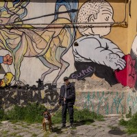 "A boy and his dog are seen near some murals outside the social center ""Ex-OPG occupato- Je so' pazzo"" in Naples, Italy on March 24, 2019."