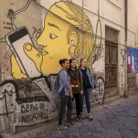 "Tourists during a street art tour organized by the cultural association ""400 ml"" in Naples, Italy on March 24, 2019. Napoli Paint Stories streetart and graffiti tour is a touristic walk in the neapolitan historical center through murales,stencils,slogans,posters and graffiti to discover urban art."
