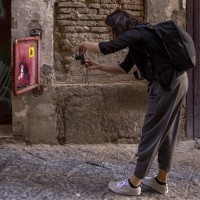 "A woman takes a picture during the street art tour organized by the cultural association ""400 ml"" in Naples, Italy on March 24, 2019. Napoli Paint Stories street art and graffiti tour is a touristic walk in the neapolitan historical center through murales, stencils, slogans, posters and graffiti to discover urban art."