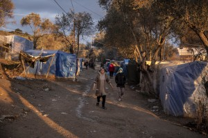 People walk inside the Moria refugee camp on the island of Lesbos in Greece on February 21, 2020. About 20000 migrants and asylum seekers – mostly coming from Afghanistan and Syria – live in the official Moria camp and in the olive grove that is located nearby.
