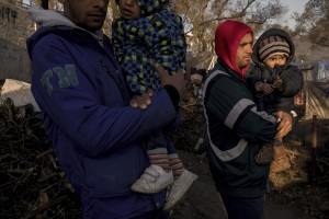 Two Afghan men with their children are seen inside the Moria refugee camp on the island of Lesbos in Greece on February 18, 2020. About 20000 migrants and asylum seekers – mostly coming from Afghanistan and Syria – live in the official Moria camp and in the olive grove that is located nearby.