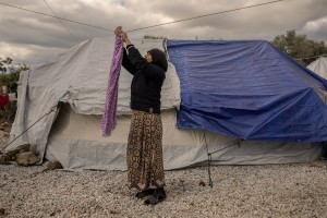 A woman puts clothes to dry inside the Moria refugee camp on the island of Lesbos in Greece on February 21, 2020. About 20000 migrants and asylum seekers – mostly coming from Afghanistan and Syria – live in the official Moria camp and in the olive grove that is located nearby.