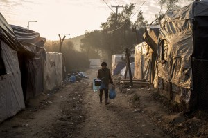A woman walks inside the Moria refugee camp on the island of Lesbos in Greece on February 19, 2020. About 20000 migrants and asylum seekers – mostly coming from Afghanistan and Syria – live in the official Moria camp and in the olive grove that is located nearby.