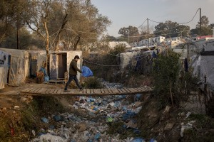 An Afghan man walks on a bridge in the Moria refugee camp on the island of Lesbos in Greece on February 19, 2020. About 20000 migrants and asylum seekers – mostly coming from Afghanistan and Syria – live in the official Moria camp and in the olive grove that is located nearby.