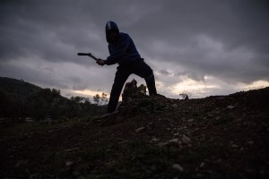A man chops wood from a tree to prepare the nght fire inside the Moria refugee camp on the island of Lesbos in Greece on February 21, 2020. About 20000 migrants and asylum seekers – mostly coming from Afghanistan and Syria – live in the official Moria camp and in the olive grove that is located nearby.