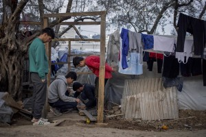 Afghan men build a tent inside the Moria refugee camp on the island of Lesbos in Greece on February 19, 2020. About 20000 migrants and asylum seekers – mostly coming from Afghanistan and Syria – live in the official Moria camp and in the olive grove that is located nearby.