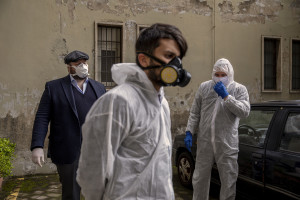 Employees of a funeral agency wear protective suits and masks during the coronavirus emergency in Naples, Italy on March 27, 2020. Although the person did not die from coronavirus, the work of funeral agency officials is among those most at risk during this emergency, as often can find in contact with corpses of people who died by coronavirus and the risk of contagion is very high.