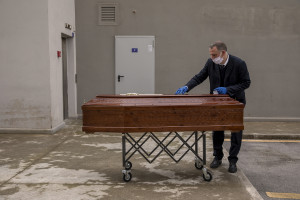 "A man is seen outside ""Ospedale del Mare"" preparing a coffin before recovering the body of a 91 years old man died for coronavirus in Naples, Italy on March 28, 2020. The work of funeral agency officials is among those most at risk during this emergency, as often can find in contact with corpses of people who died by coronavirus and the risk of contagion is very high."
