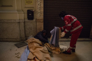 A volunteer from the Italian Red Cross gives a blanket to a homeless person in Naples, Italy on April 2, 2020. Homeless are experiencing a double emergency: the first one due to their condition, the second one linked to the spread of the coronavirus that caused the closure of many assistance centers because of possible contagion.
