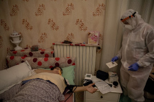 A nurse of the Italian Red Cross checks Lesya's pressure after an emergency call received in the night, for suspected coronavirus symptoms in Naples, Italy on April 7, 2020.