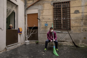 A woman and a man rest after disinfecting the courtyard of a building on the eighth day of unprecedented lockdown across of all Italy imposed to slow the spread of coronavirus in Naples, Southern Italy on March 17, 2020.