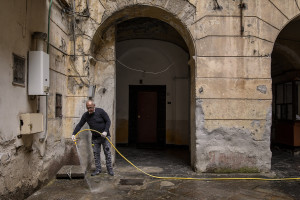 A man disinfects the courtyard of a building on the eighth day of unprecedented lockdown across of all Italy imposed to slow the spread of coronavirus in Naples, Southern Italy on March 17, 2020.