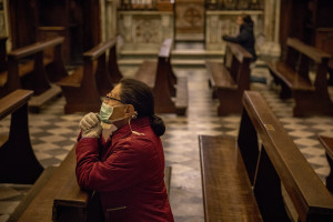 "A woman wearing a mask prays inside the ""Carmine"" church on the fifth day of unprecedented lockdown across of all Italy imposed to slow the spread of coronavirus in Naples, Southern Italy on March 14, 2020."