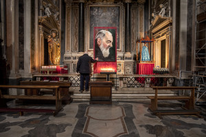 "A man prays in front of a painting depicting Saint Pio of Pietrelcina inside the ""Gesù Nuovo"" church on the third day of unprecedented lockdown across of all Italy imposed to slow the spread of coronavirus in Naples, Southern Italy on March 12, 2020."
