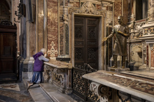 "A woman wearing a mask prays in front of the Saint Giuseppe Moscati statue inside the ""Gesù Nuovo"" church on the third day of unprecedented lockdown across of all Italy imposed to slow the spread of coronavirus in Naples, Southern Italy on March 12, 2020."