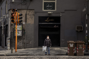A woman wearing a mask standing at the traffic light on the eighth day of unprecedented lockdown across of all Italy imposed to slow the spread of coronavirus in Naples, Southern Italy on March 17, 2020.