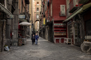 People wearing masks walk in a deserted San Gregorio Armeno street during the ninth day of unprecedented lockdown across of all Italy imposed to slow the spread of coronavirus in Naples, Southern Italy on March 18, 2020.