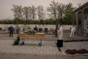 A priest blesses the coffin of a 47 years old man died of coronavirus, inside the cemetery of Locate Bergamasco, province of Bergamo, Northern Italy on April 16, 2020.