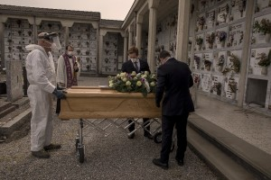 Funeral agency employees introduce the coffin of a 47 years old man died of coronavirus, inside a tomb in the cemetery of Locate Bergamasco, province of Bergamo, Northern Italy on April 16, 2020.
