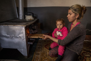 Selma, 18 years old burns wood while holding up her daughter inside her house in the area of Shutka in Skopje, North Macedonia on February 29, 2020. During the winter Selma, like many others households, burns coal, scrap wood, textiles or trash in order to keep warm. This obsolete heating system is one of the biggest contributors to air pollution in the country. Although the electricity tariffs in Macedonia are among the lowest in Europe, energy can cost a third or even half of a citizen's  average monthly salary. This is the reason why many residents burn wood to heat their home, often buying it on the black market where it costs less, but is more toxic for the environment.