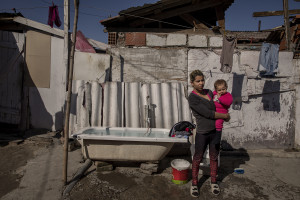 Selma, 18 years old and her daughter are seen outside their house in the area of Shutka in Skopje, North Macedonia on February 29, 2020. During the winter Selma, like many others households, burns coal, scrap wood, textiles or trash in order to keep warm. This obsolete heating system is one of the biggest contributors to air pollution in the country. Although the electricity tariffs in Macedonia are among the lowest in Europe, energy can cost a third or even half of a citizen's  average monthly salary. This is the reason why many residents burn wood to heat their home, often buying it on the black market where it costs less, but is more toxic to the environment.