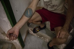 """Gaetano Ippolito, 46 years old shows a tattoo depicting the logo of Napoli soccer in the """"Rione Sanità"""" in Naples, Italy on June 17, 2020. Since the pandemic broke out, Gaetano has no longer been able to find any type of job, even on an occasional basis. Popular neighborhoods are those that more than others are suffering from the economic crisis generated by the coronavirus. The rate of poverty and unemployment that was higher than the national average in Southern Italy even before the pandemic, increased following the lockdown imposed by the government to counter the spread of the coronavirus, which blocked the country's economy for more than two months."""