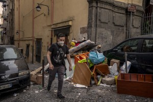 """A boy walks among the garbage in the """"Quartieri Spagnoli"""" in Naples, Italy on June 16, 2020. Popular neighborhoods are those that more than others are suffering from the economic crisis generated by the coronavirus. The rate of poverty and unemployment that was higher than the national average in Southern Italy even before the pandemic, increased following the lockdown imposed by the government to counter the spread of the coronavirus, which blocked the country's economy for more than two months."""