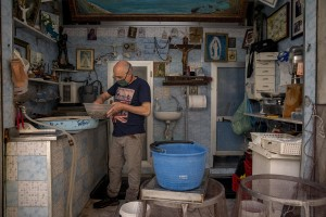 """Vincenzo, 64 years old is seen at work inside his fish shop in the """"Rione Sanità"""" in Naples, Italy on June 17, 2020. Popular neighborhoods are those that more than others are suffering from the economic crisis generated by the coronavirus. The rate of poverty and unemployment that was higher than the national average in Southern Italy even before the pandemic, increased following the lockdown imposed by the government to counter the spread of the coronavirus, which blocked the country's economy for more than two months."""