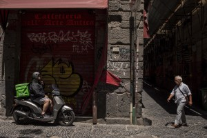 A rider (left) and a man (right) are seen in a street of the historical center of Naples, Italy on June 15, 2020.